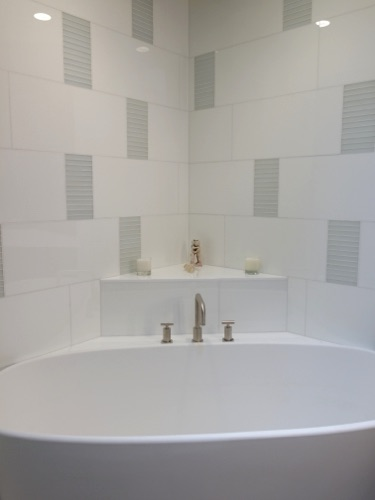 "White ""glassos"" tile with acid etched mosaic accents. Shelf for sculpture behind tub."
