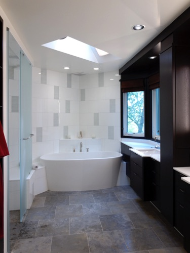 View of tub, vanities to right; shower on left. Materials are limestone floors, glass tile walls.